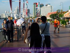 Turisti intenti a scattare foto sulla banchina dell'Asiatique.